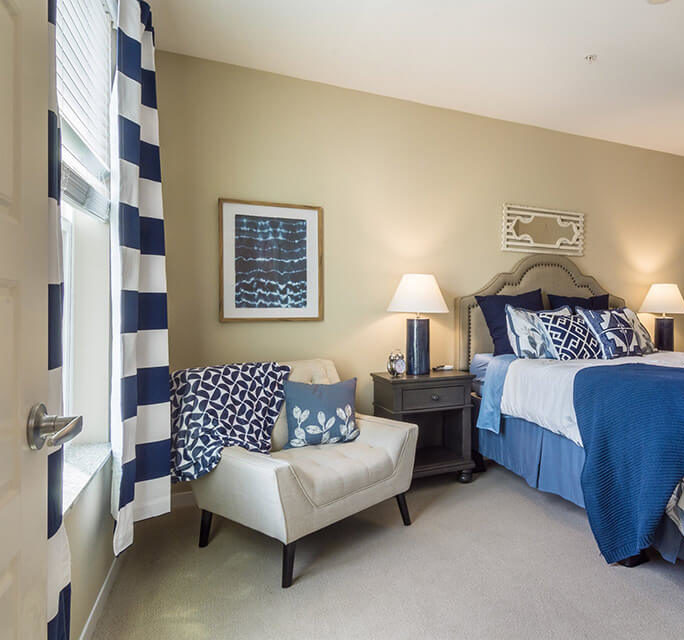 Bedroom in Park Creek model apartment with view of window on left, chair and bed in the middle and bathroom on right