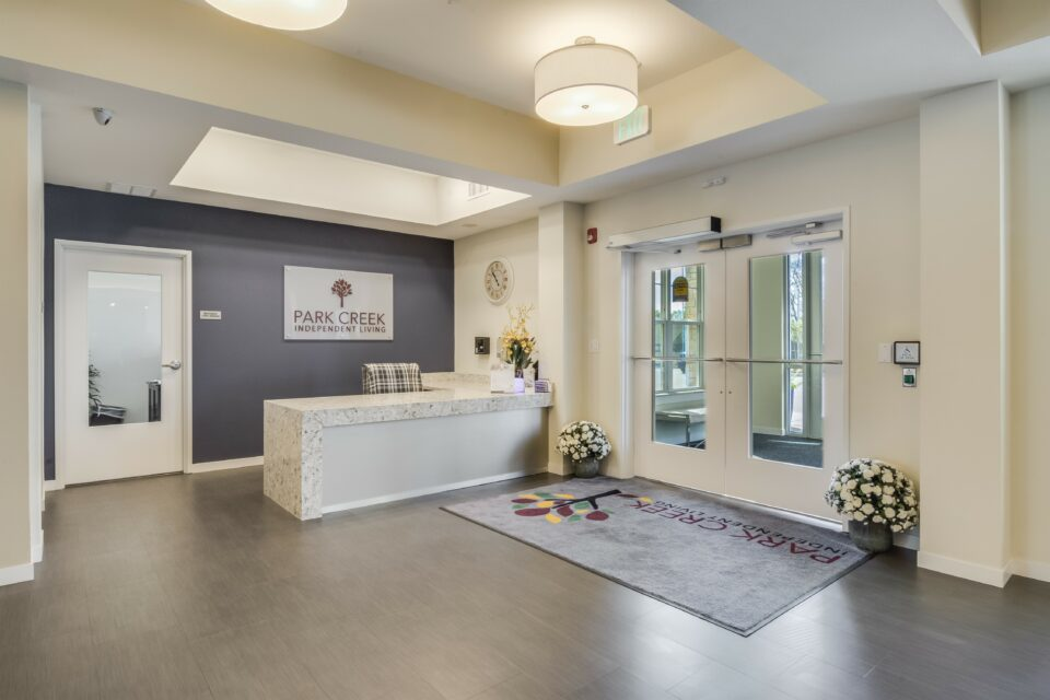 Lobby of the community with ivory walls and gray accent wall behind front desk overlaid with granite