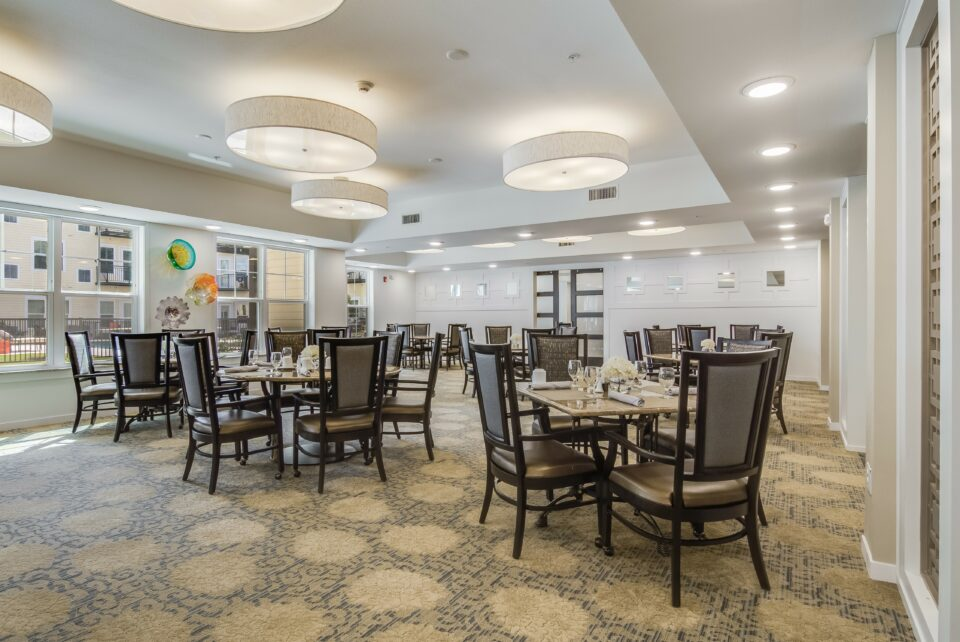 Dining room with four top tables and chairs, circular patterned carpet, large white round light fixtures