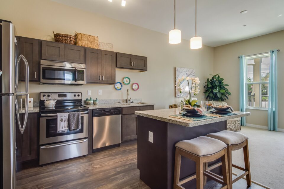 Model apartment kitchen with granite island, two barstools, dark cabinets and stainless steel appliances