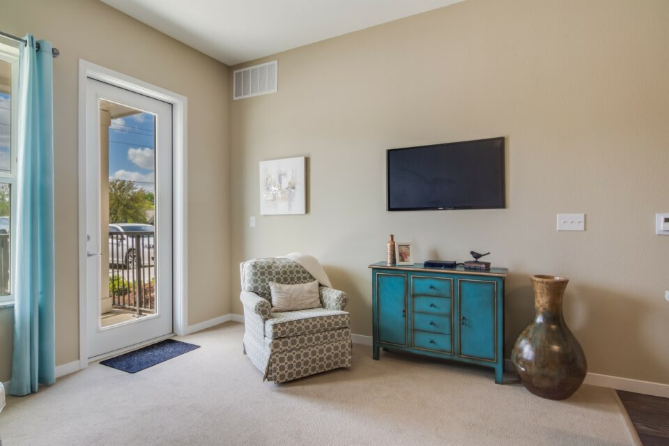 Model apartment bedroom with beige and teal decor, patio door and window at left, chair and large screen TV on wall at right
