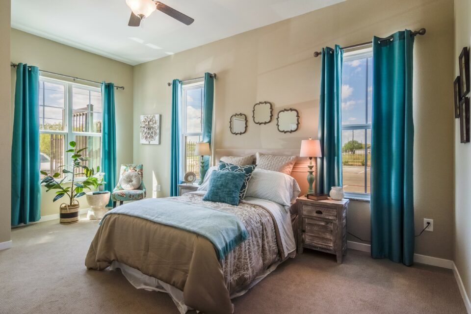 Model apartment bedroom with beige and teal bedding and two windows on either side of bed, teal curtains