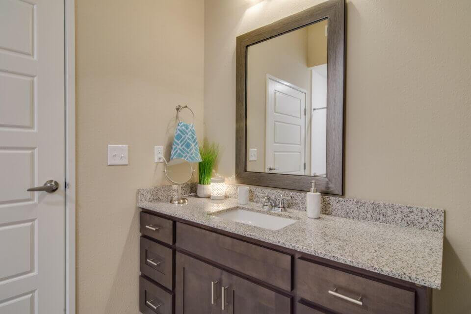 Model apartment bathroom with granite vanity, sink and mirror