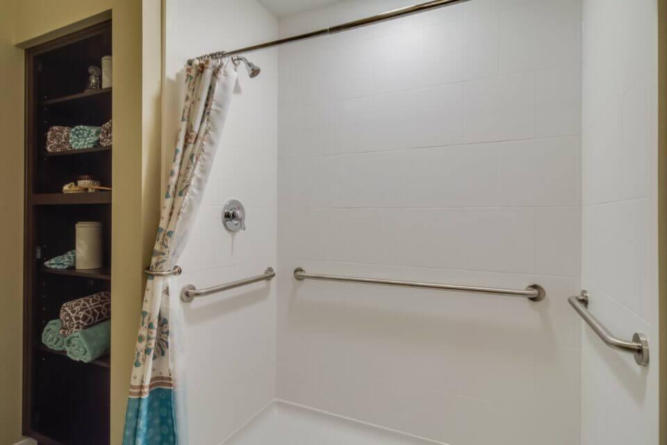 Model apartment shower with grab bars, dark wood linen shelves to left
