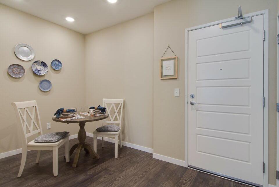 Two bedroom apartment foyer with eat in kitchen table and chairs to left and front door at right