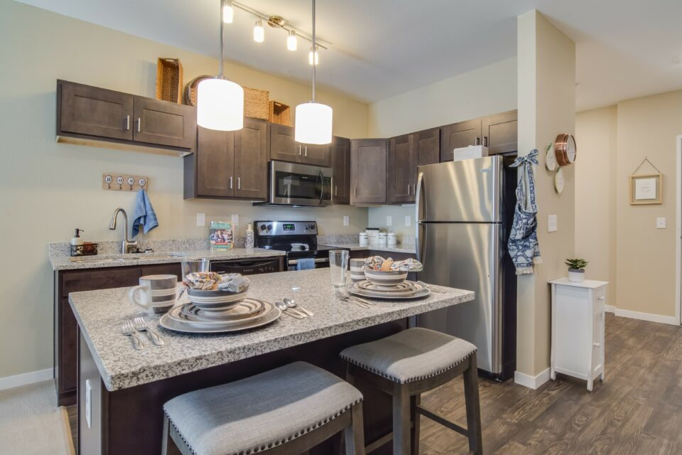 Model apartment kitchen with granite island at center with two barstools, dark cabinets and stainless steel appliances