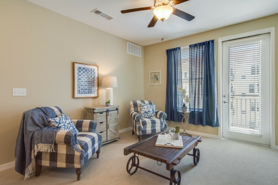 Model apartment living room with two navy and white plaid chairs, coffee table, window and balcony door to right