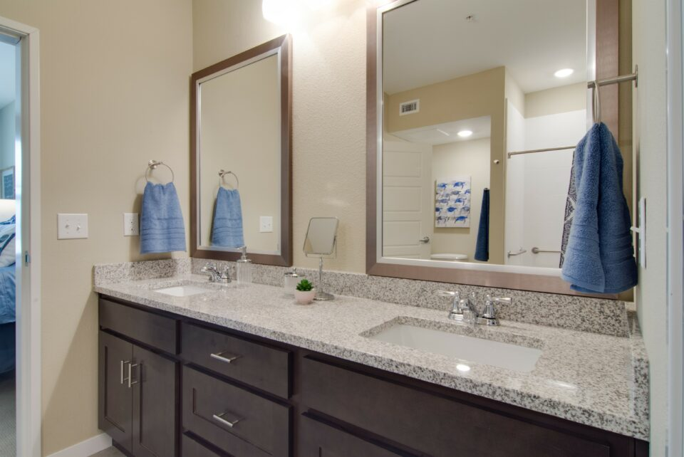 Model apartment bathroom with dual sink vanity and dual mirrors