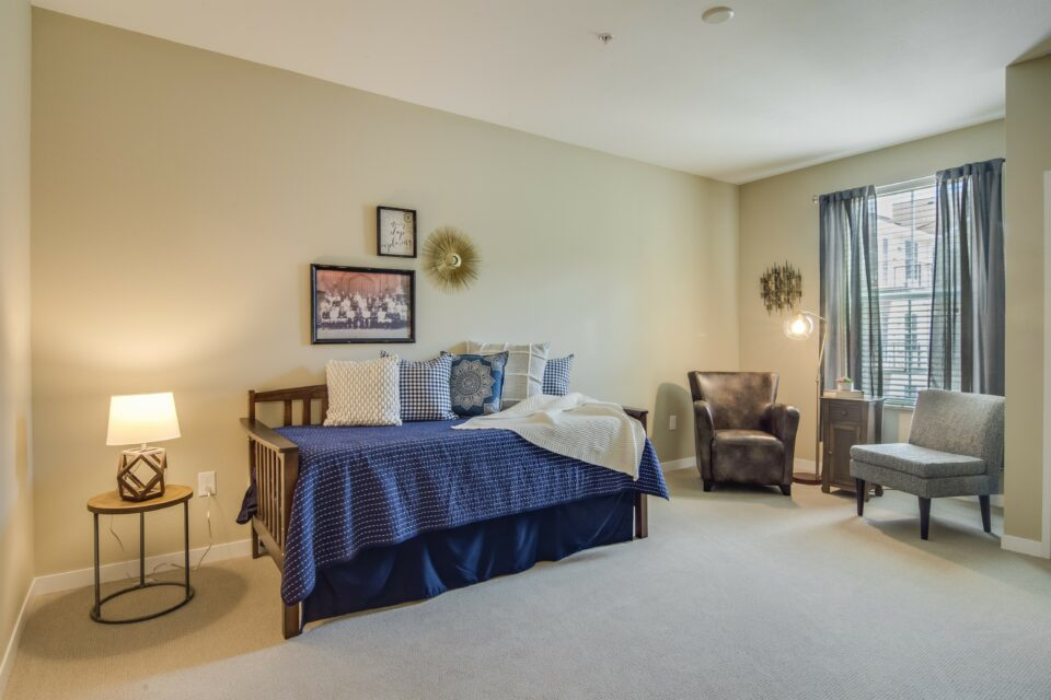 2nd Bedroom of two bedroom model apartment, navy bedding and two chairs by window at right