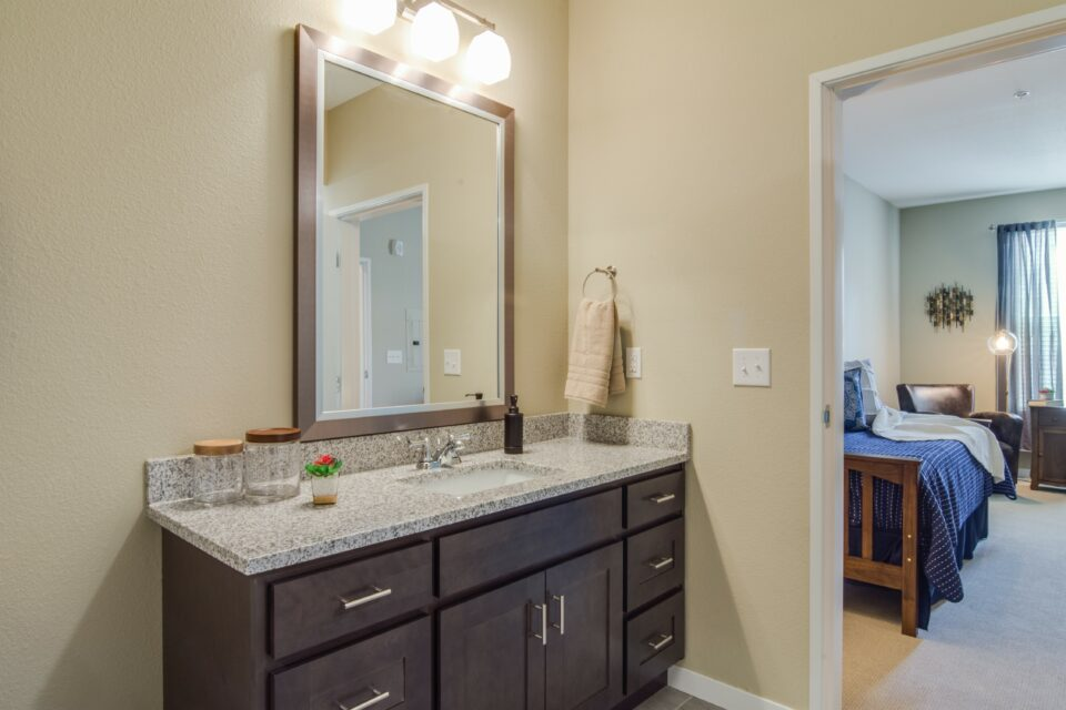 Model apartment with bathroom vanity sink and mirror at left and bedroom to right