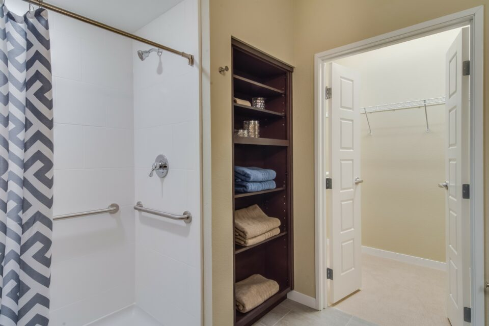 Model apartment with shower at left and linen shelves and closet to right