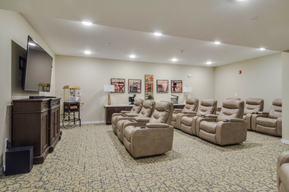 Community movie theater room with large brown leather reclining seats with cupholders, large flat screen TV and popcorn machine