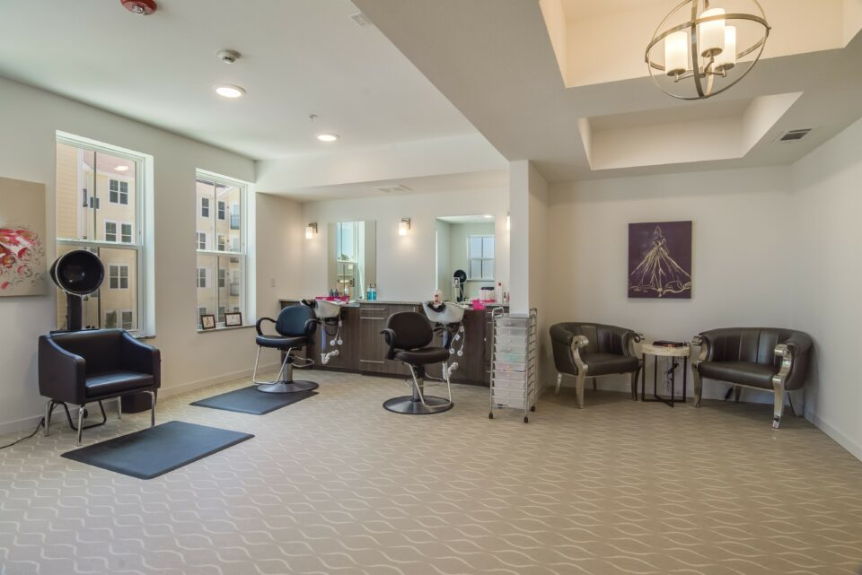 Beauty slaong with two waiting chairs at right dryer at left and two salon chairs with sinks and mirrors at center