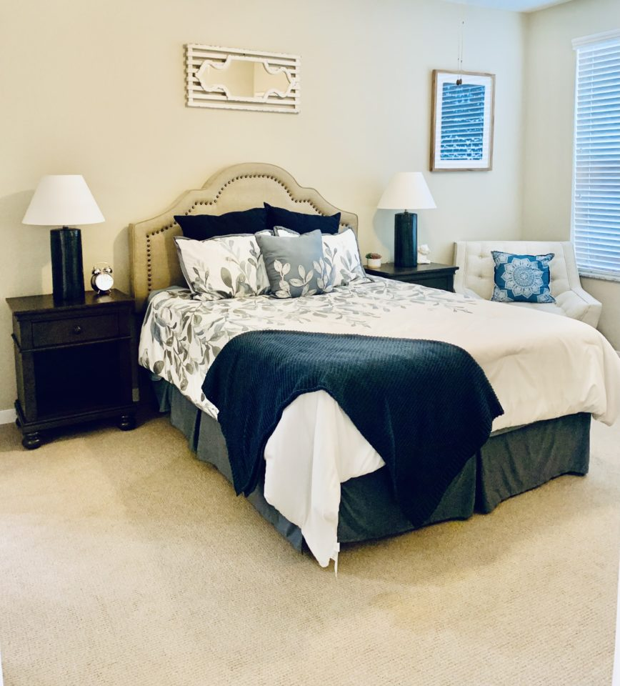 Bedroom in Park Creek model apartment with view of chair and window on right