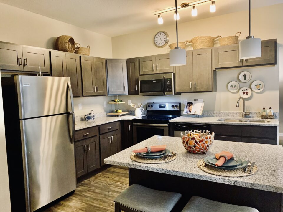 Model apartment kitchen with granite island and barstools at center, stainless steel fridge at left and dark wood cabinetry