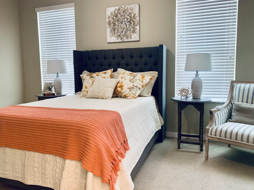 Model apartment bedroom with orange and white bedding, chair on right and windows on each side of bed