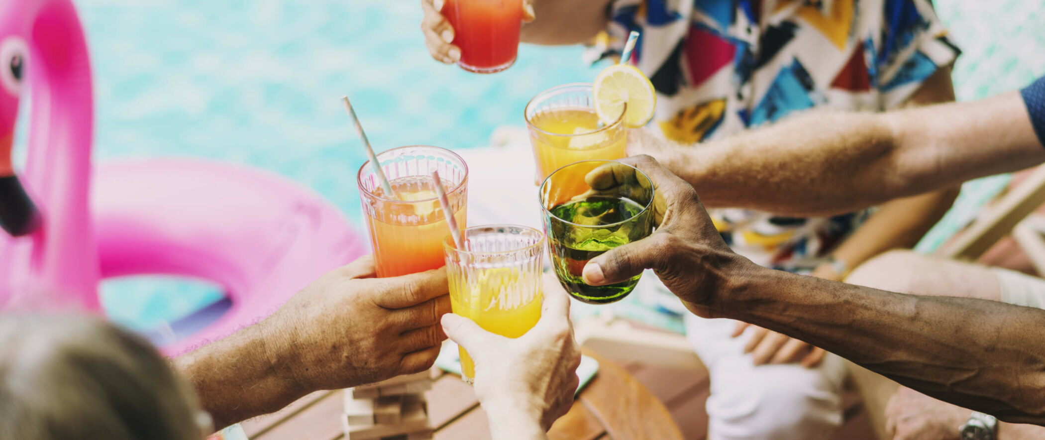 Closeup of the arms of five friends cheering with mixed drinks poolside
