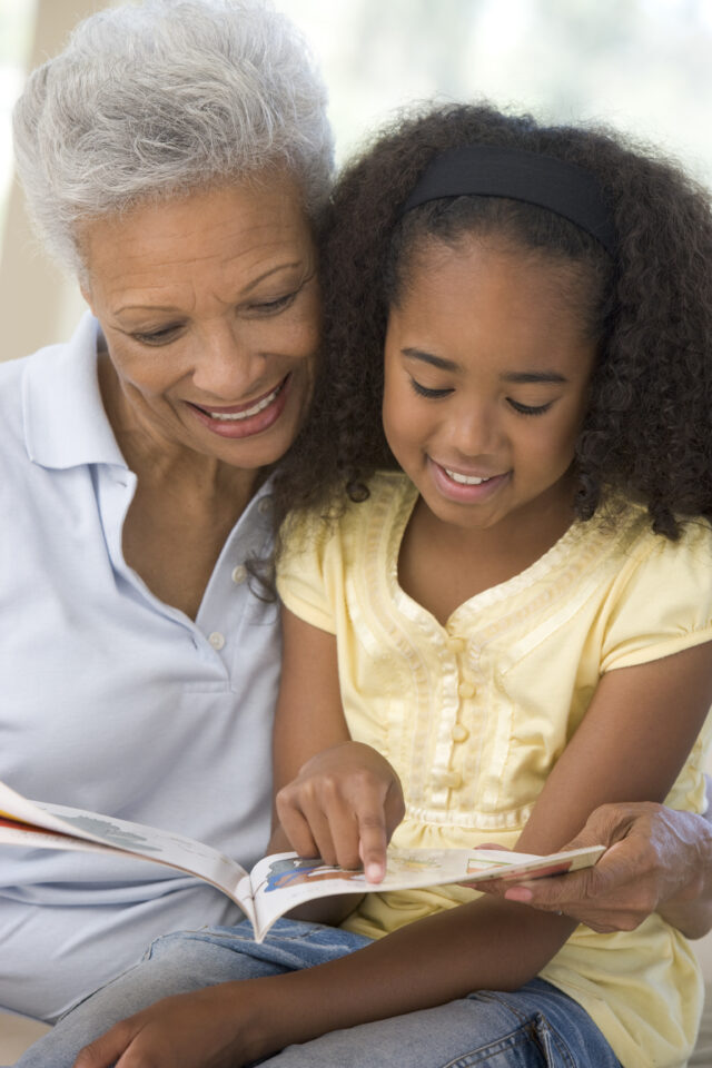 Senior woman reads to granddaughter in yellow shirt