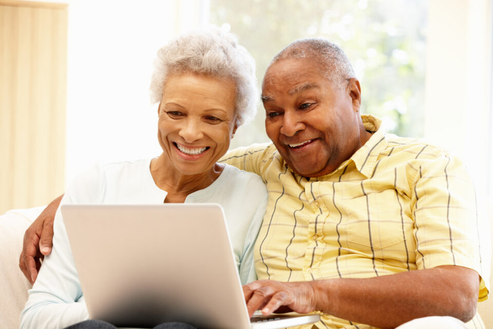 Smiling senior couple sit on couch together looking at laptop