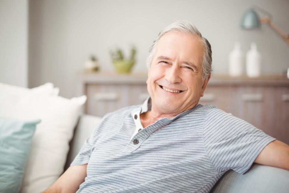Senior man smiling and sitting on couch with white and teal pillows
