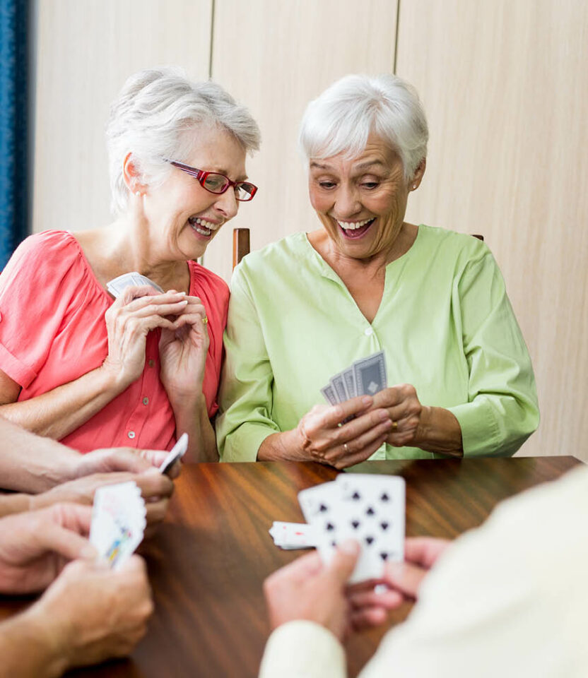 Senior women at a table playing cards