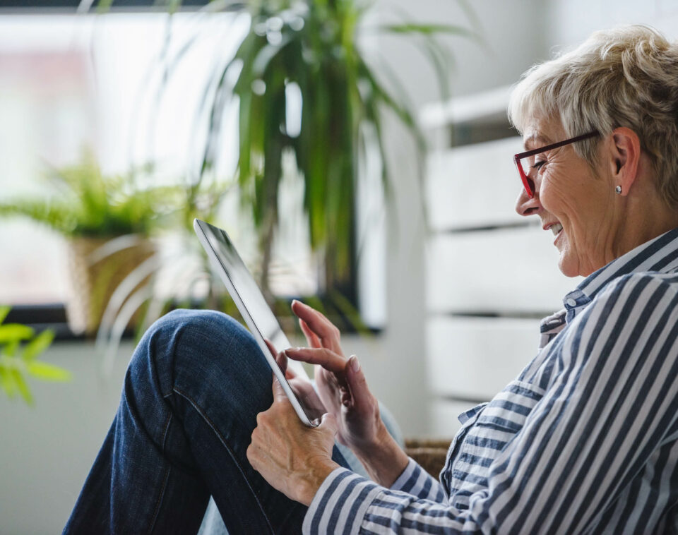Senior woman sits on the floor working on a tablet