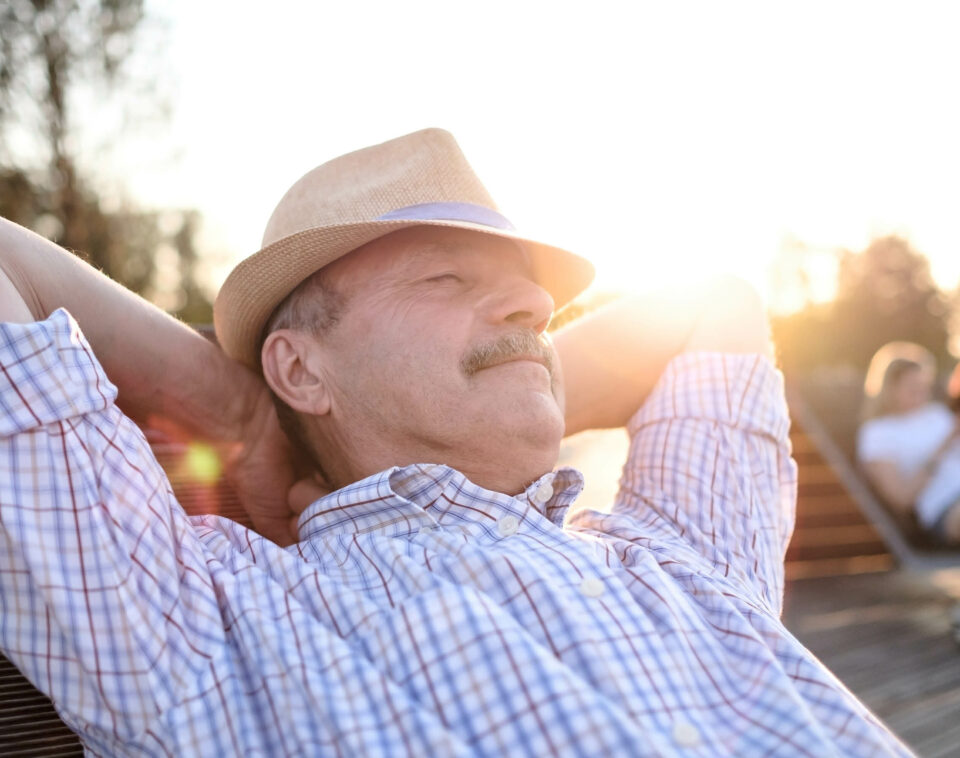 Man lays back in an outside chair with hands behind his head enjoying the sunshine.