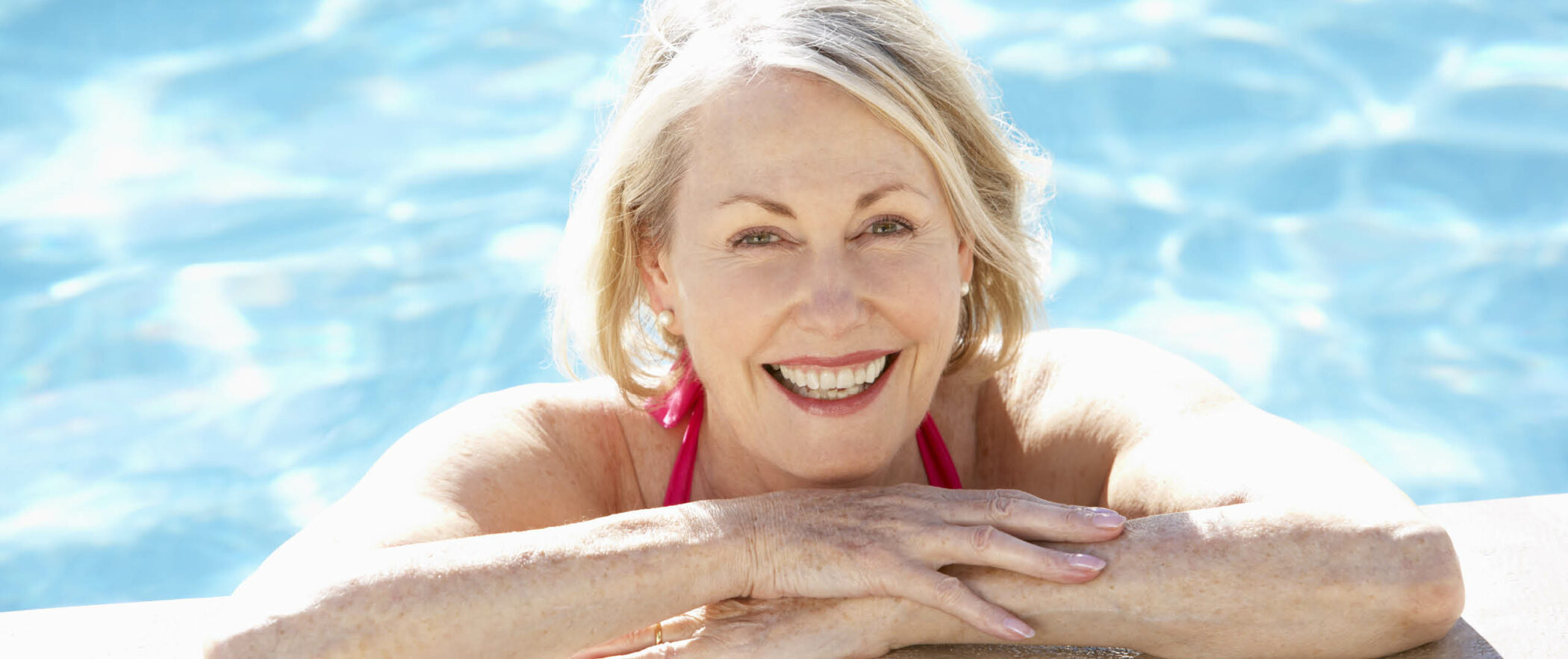 Senior woman leans chin on folded arms at edge of pool with sparkling blue water behind her