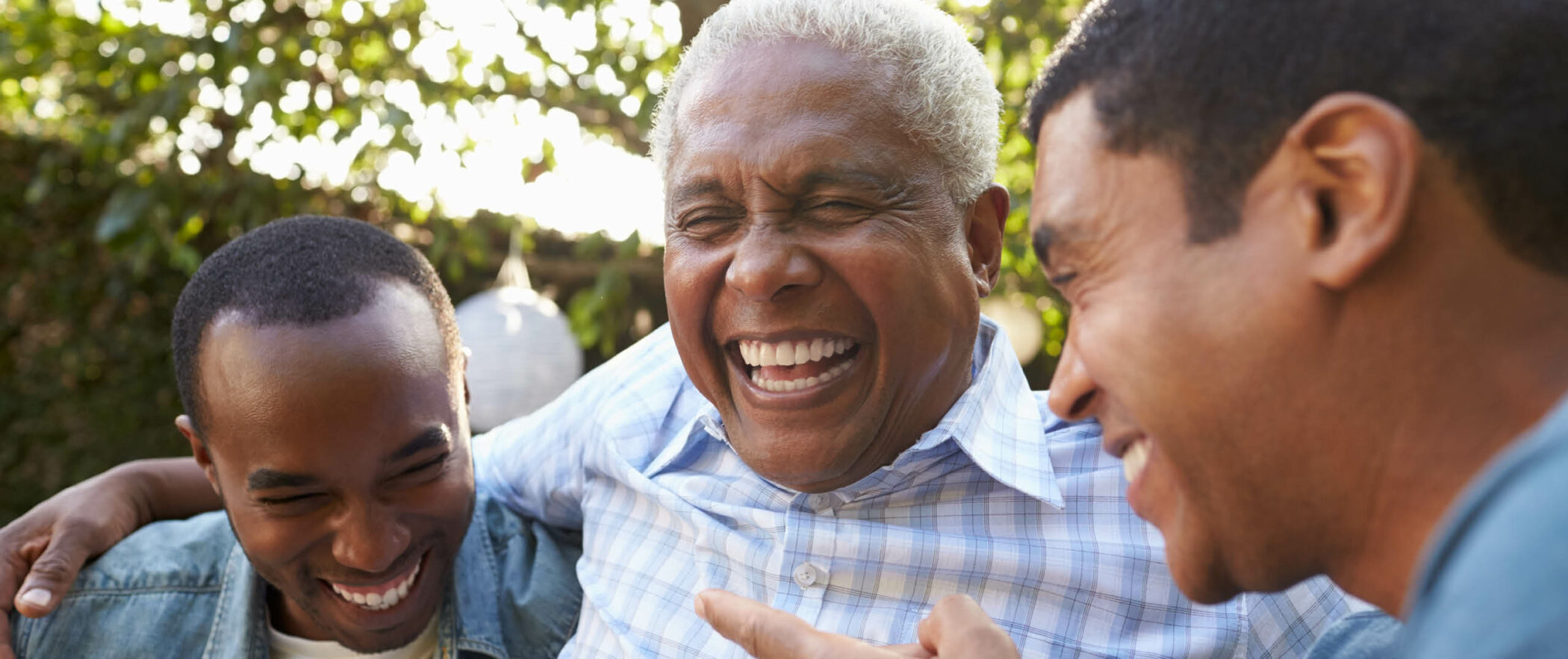 Senior man laughing on patio with two adult sons on each side and green trees behind
