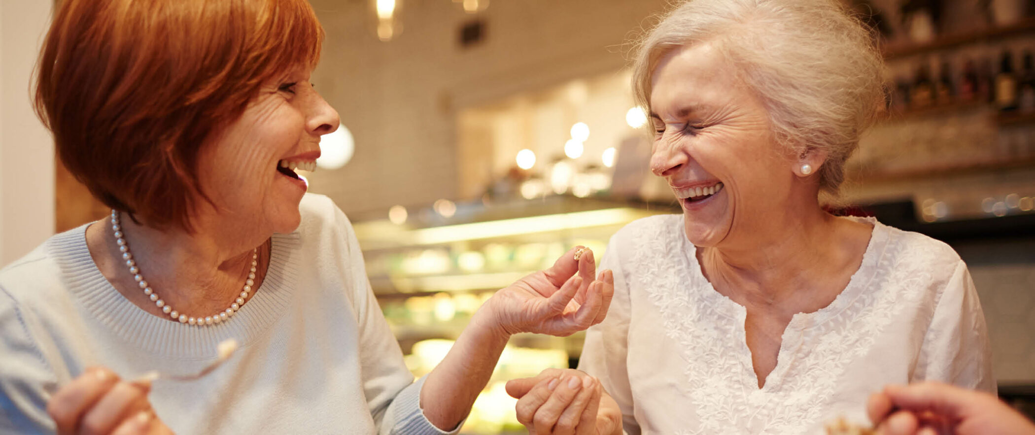 Senior women enjoy coffee and dessert while smiling and laughing